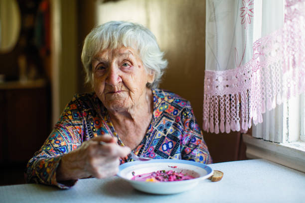 An elderly woman eating soup sitting at a table in the house. An elderly woman eating soup sitting at a table in the house. hungry stock pictures, royalty-free photos & images
