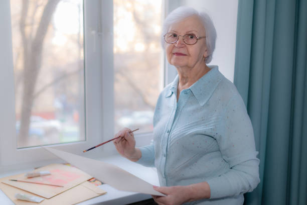 An elderly woman is going to draw stock photo