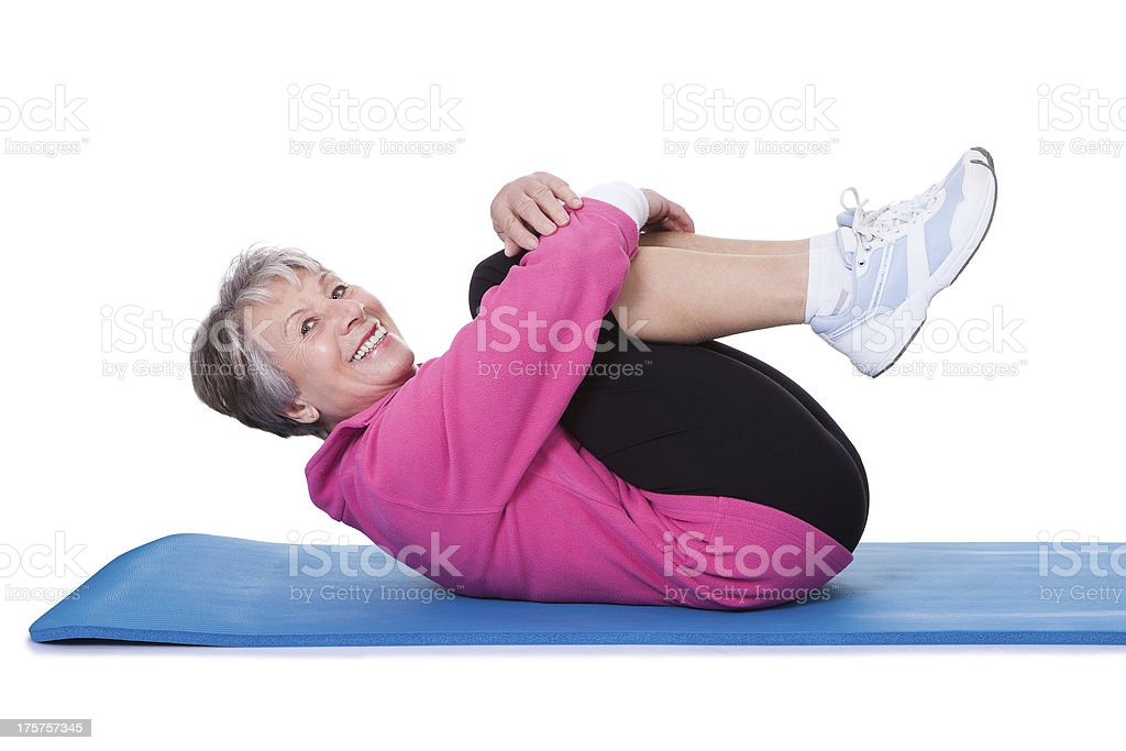 An elderly woman laying on a mat while exercising stock photo