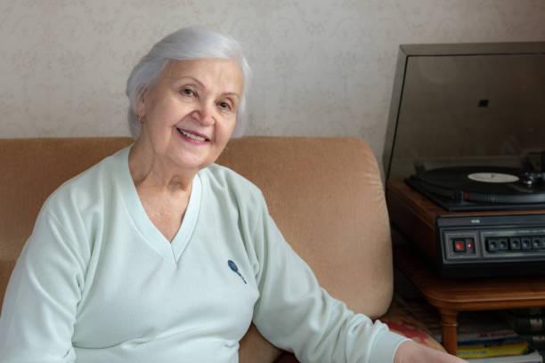 An elderly woman listening to music stock photo