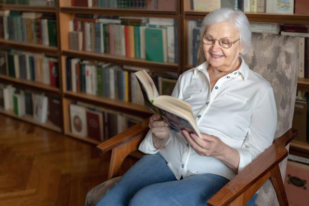 An elderly woman reading a book stock photo