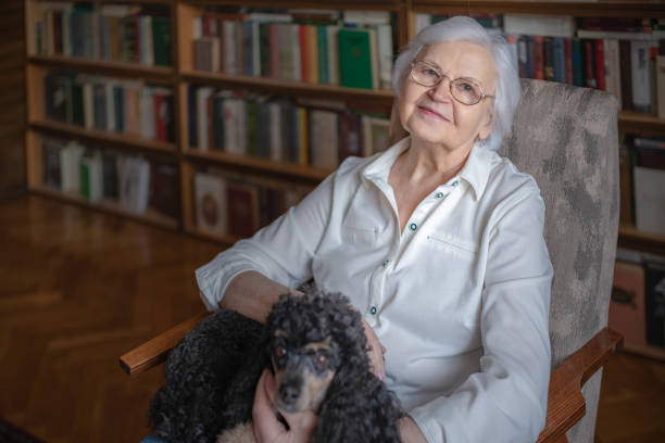 An elderly woman sitting in a chair with her pet stock photo