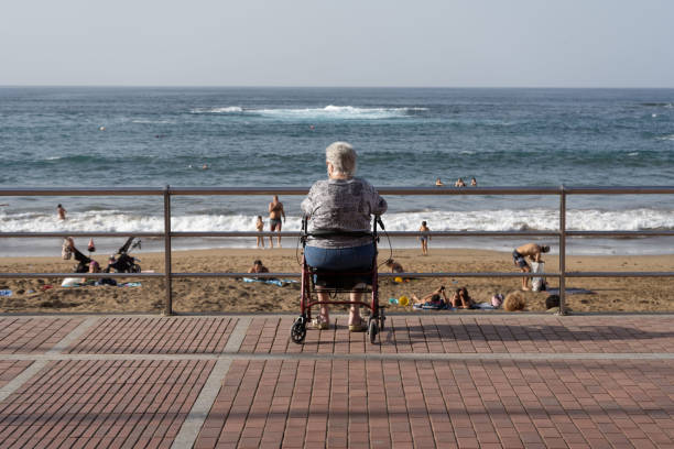 An elderly woman sitting in her walking frame watching people bathe on Las Canteras beach stock photo