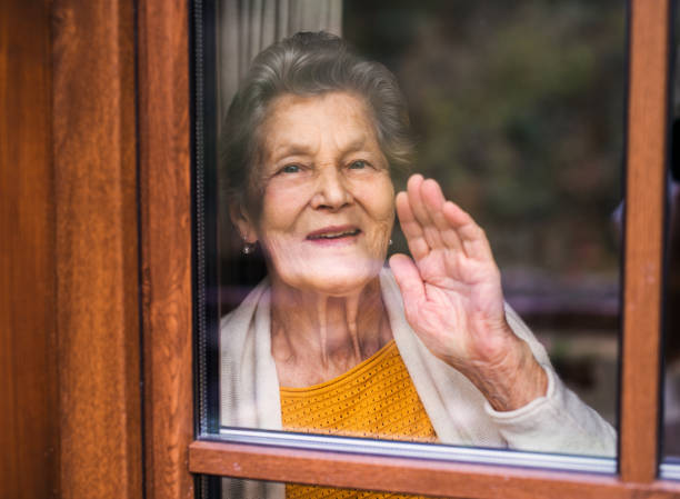 an elderly woman standing by the window, looking out. shot through glass. - sventolare la mano foto e immagini stock