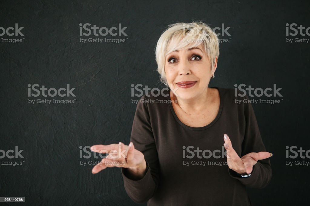 An elderly woman who was deceived, or she does not understand what happened to her, shows by gesture a question mark with her hands stock photo