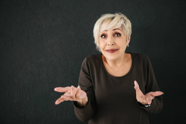 an elderly woman who was deceived, or she does not understand what happened to her, shows by gesture a question mark with her hands - confusion stock photos and pictures