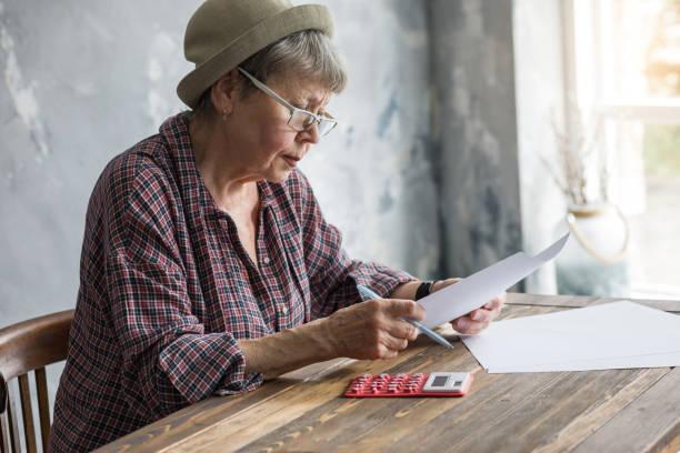 an elderly woman with financial documents and a calculator. - pensionati lavoratori foto e immagini stock