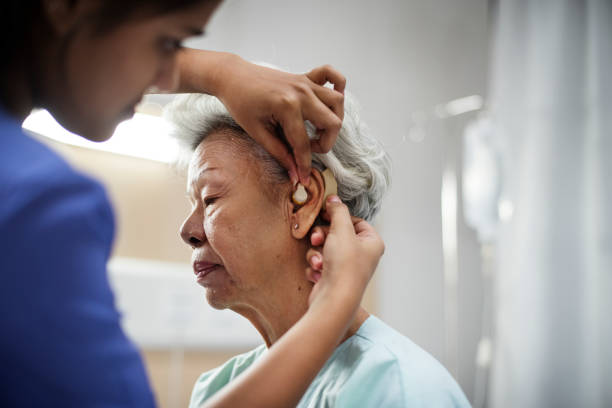 An elderly woman with hearing aid stock photo