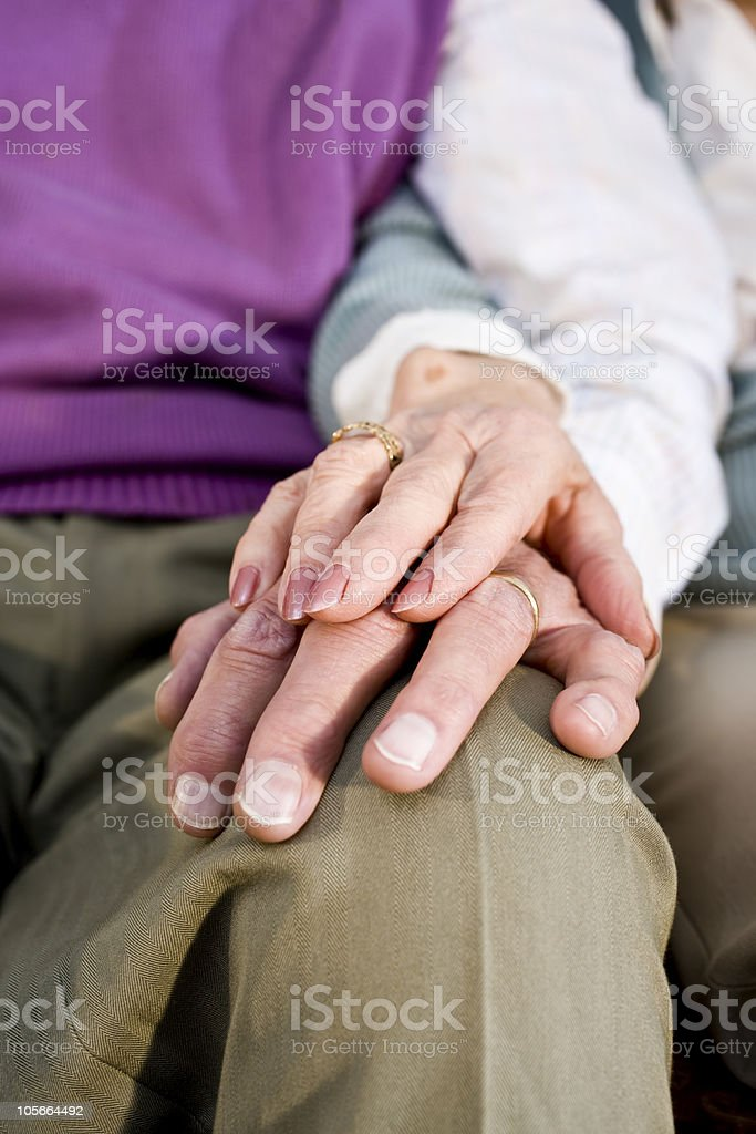 An elderly woman's hand on an elderly man's hand on his knee royalty-free stock photo