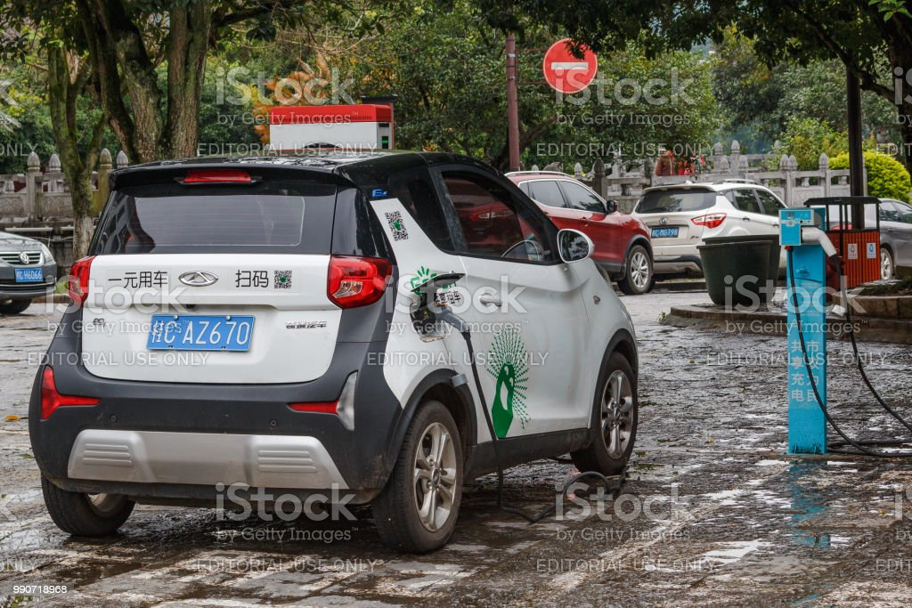 An electric car charging on the street in tourist city Yangshuo of China. stock photo