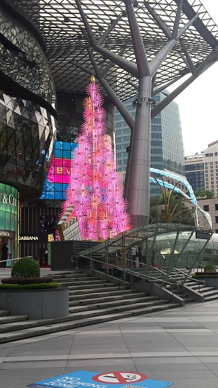 An electric Christmas tree in pink, illuminated on daytime in front of a Mall for top trade marks on Orchard Road, Singapore, on November 11, 2019