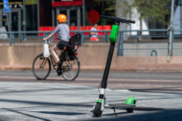 An electric scooter waiting for user on the city street. A bicyclist riding by at the background. stock photo