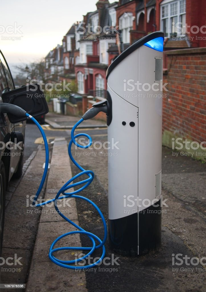 An electric vehicle being charged at a charging station at a...