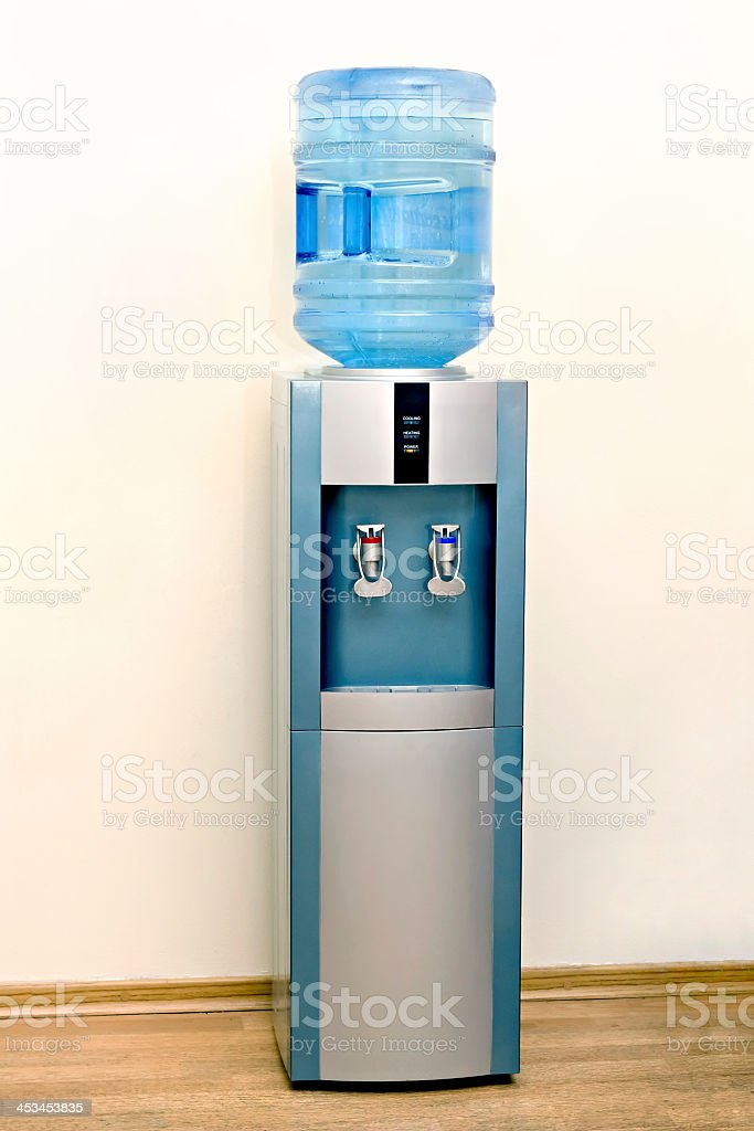 An electric water cooler in front of a white wall stock photo