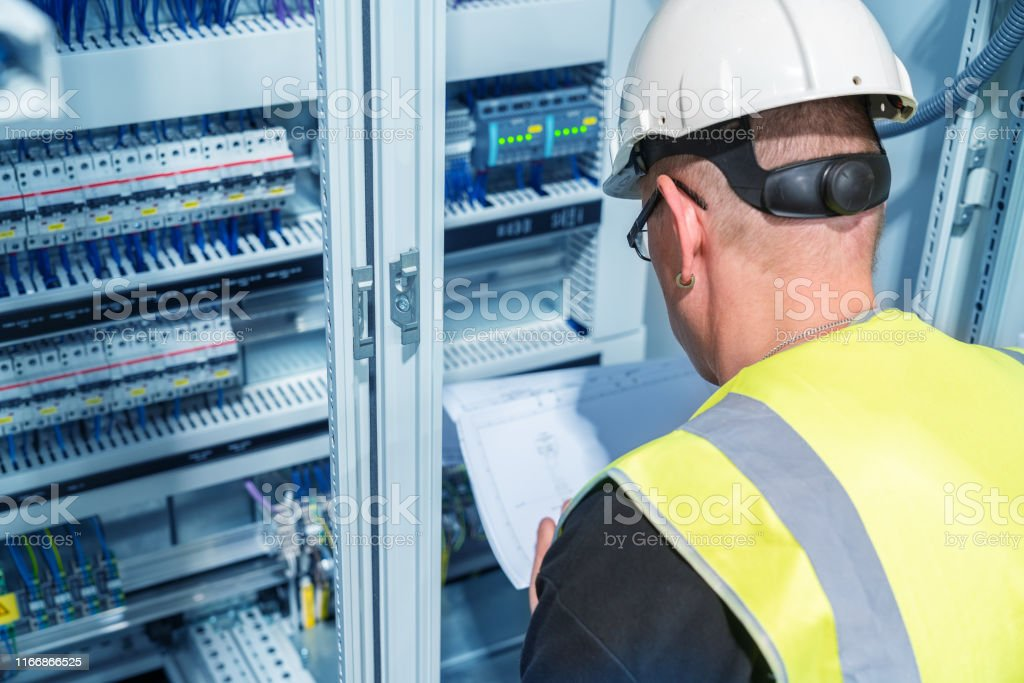 an electrical engineer reads a wiring diagram in a control cabinet stock  photo  download image now