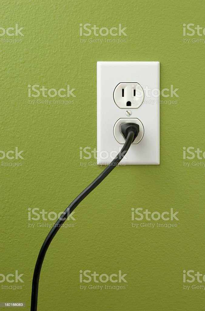 An electrical outlet with a plug inserted royalty-free stock photo