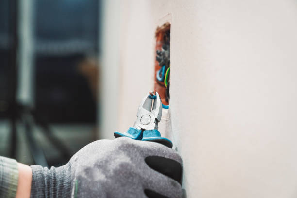An electrician clamping the wires in the wall stock photo
