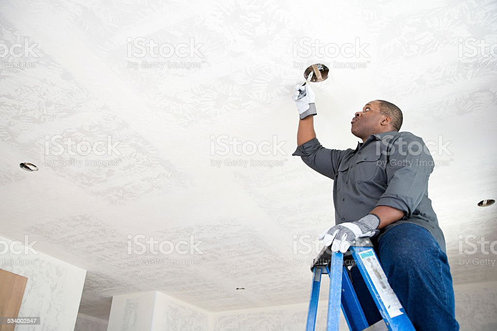 An electrician fixing wires stock photo