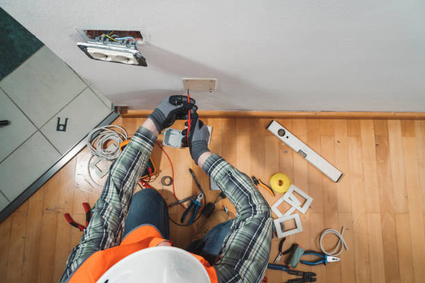 An electrician screwing a lid on the wall stock photo