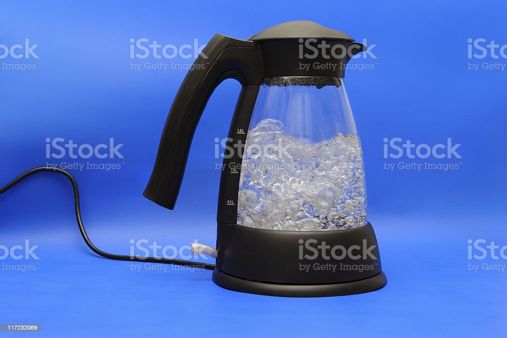 An electronic kettle with boiling water on a blue background stock photo