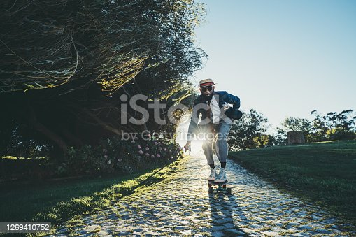 A fancy mature bearded black guy in a fashionable costume with a hat and a necktie, with a golf club in his hand and a cigar in his mouth, is rolling on a skateboard on paving-stone on the sunset