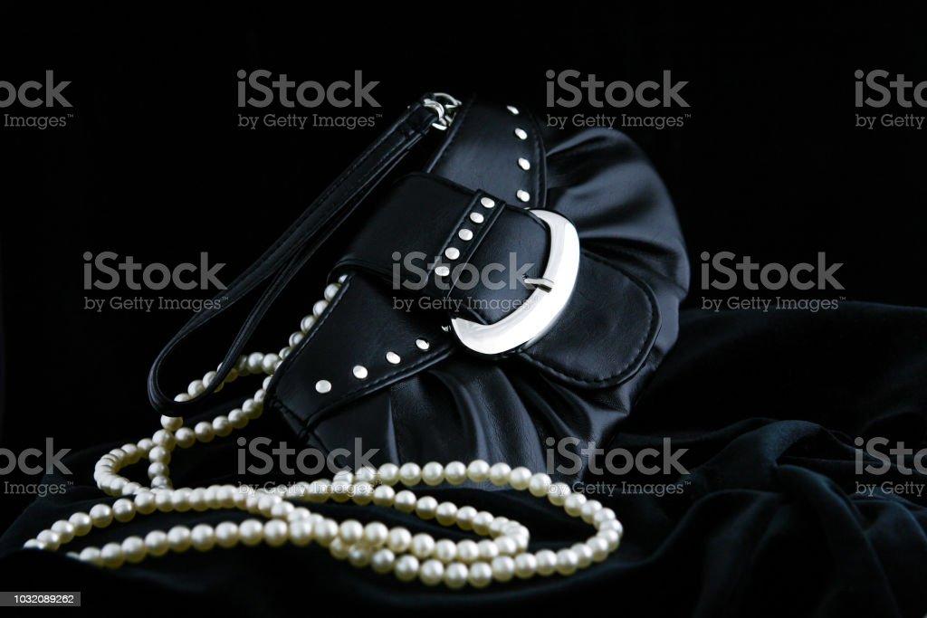 69e80c18939 Saco de noite de um elegante, couro preto da mulher deitada em um veludo  preto