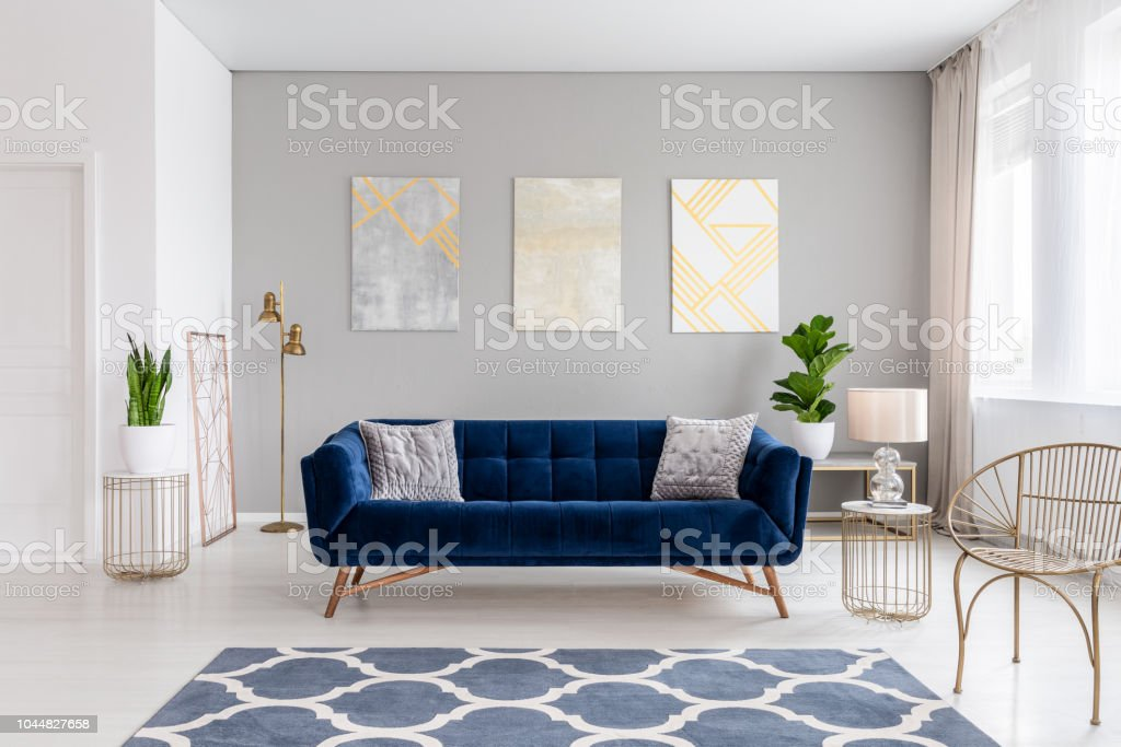 An Elegant Navy Blue Sofa In The Middle Of A Bright Living Room Interior With Gold Metal Side Tables And Three Paintings On A Gray Wall Real Photo Stock Photo Download