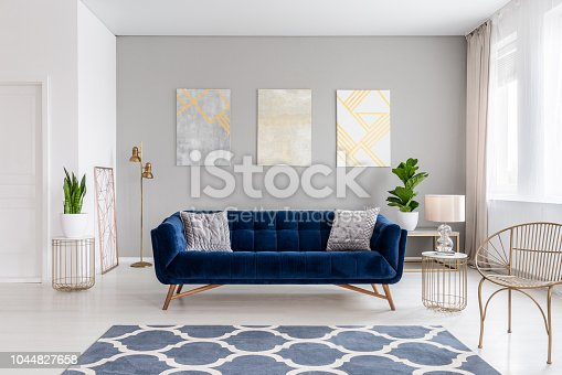 istock An elegant navy blue sofa in the middle of a bright living room interior with gold metal side tables and three paintings on a gray wall. Real photo. 1044827658