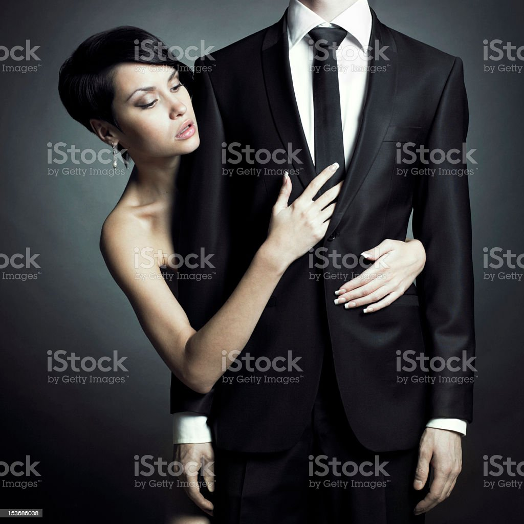 An elegant woman hugging the chest of a still man in tuxedo royalty-free stock photo