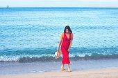 An elegant woman walking on the beach