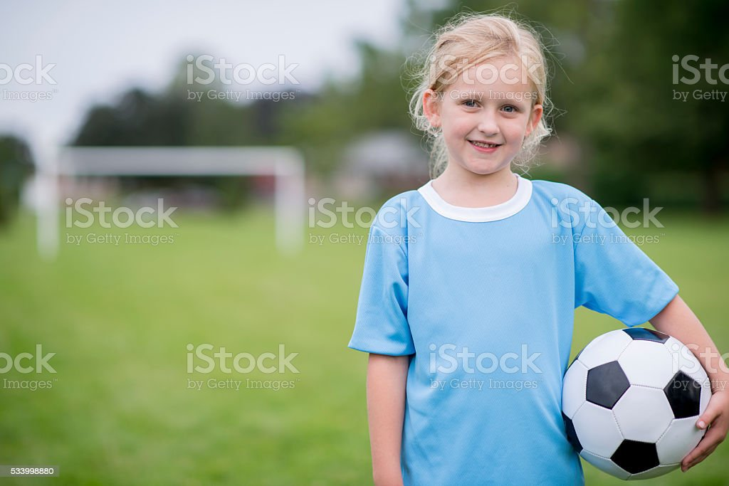 An elementary age girl is standing with a soccer ball stock photo