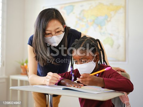 An elementary aged school student and teacher in a classroom wearing a mask for protection against infectious disease.
