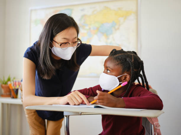 An Elementary School Student and Teacher in a Classroom stock photo