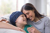 An elementary-age boy battling cancer sits with his mother on the couch