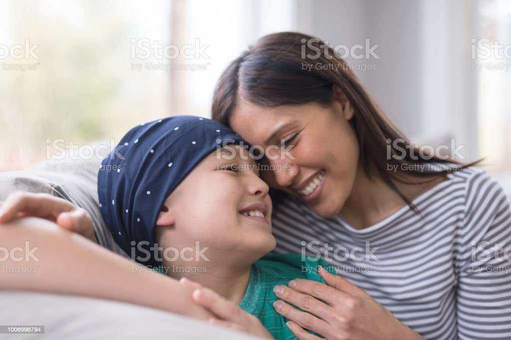An elementary-age boy battling cancer sits with his mother on the couch stock photo