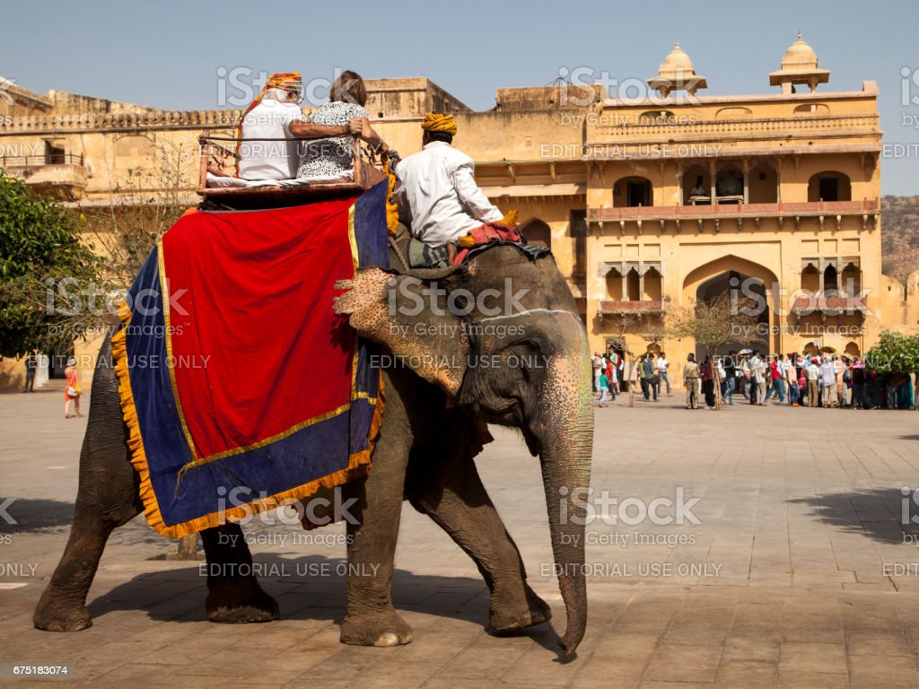 An elephant carries tourists at the entrance to the Amber Fort near Jaipur, India stock photo