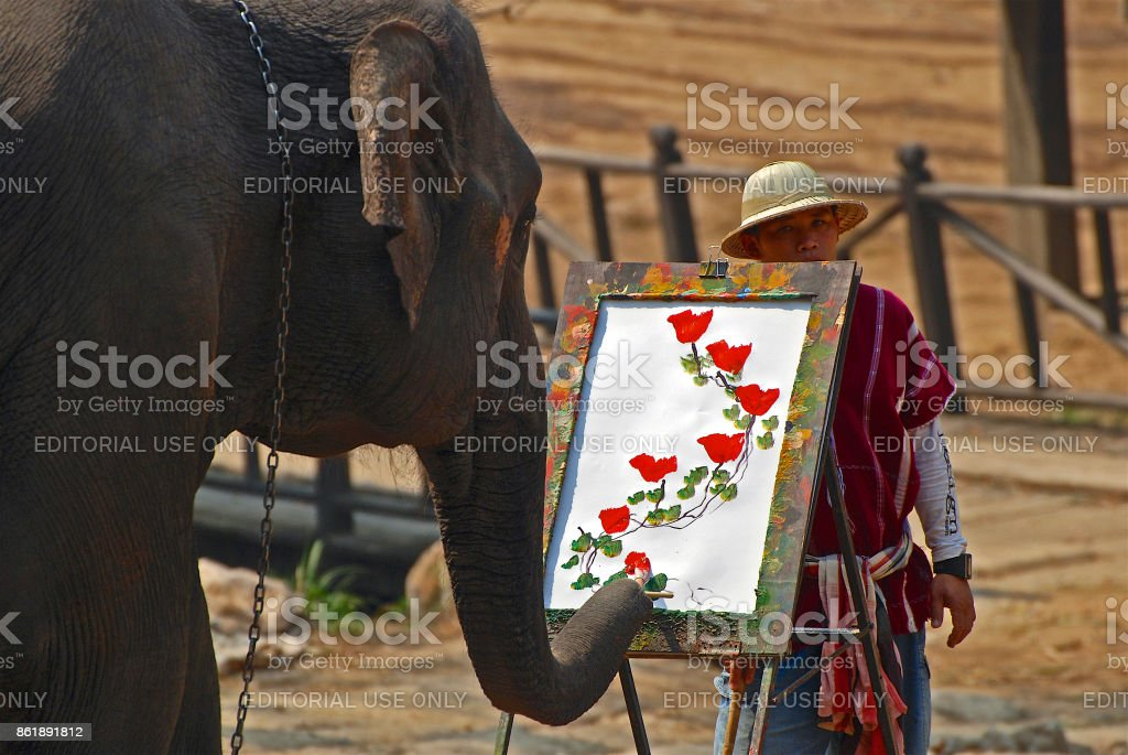 An elephant paints a picture of flowers stock photo