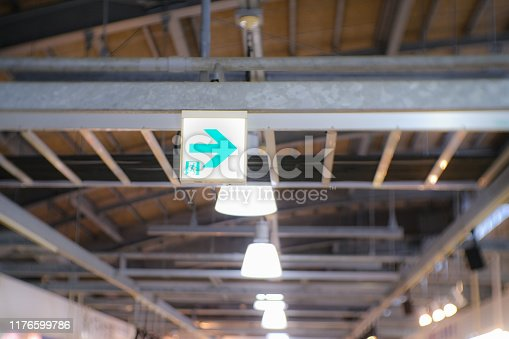 1182906669istockphoto an emergency exit sign hanging under a steel beam with blurred background 1176599786