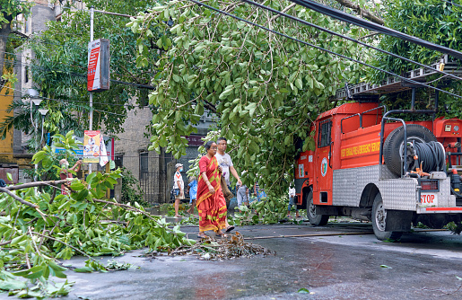 A fire and emergency service vehicle standing in middle of street, among messy surroundings of fallen tree branches and cluttered power cables. Two people are seen walking there.\n\nThe day after cyclone Amphan hit Kolkata, as well as whole state of West Bengal. Photo taken at Deshapriya Park, Kolkata on 05/21/2020.