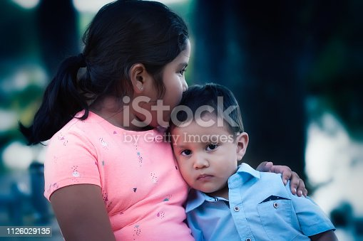 An emotionally hurt young boy leaning on her older sister and being comforted by her kiss and support.