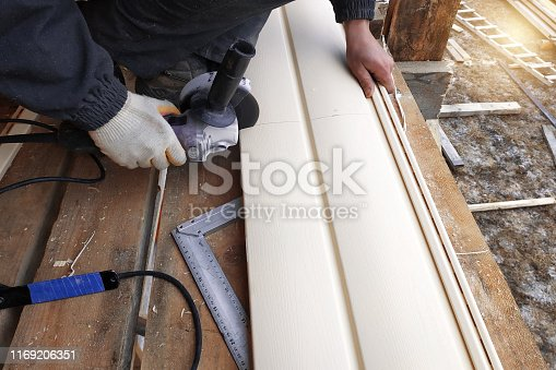 An employee cuts siding to the required size 2019
