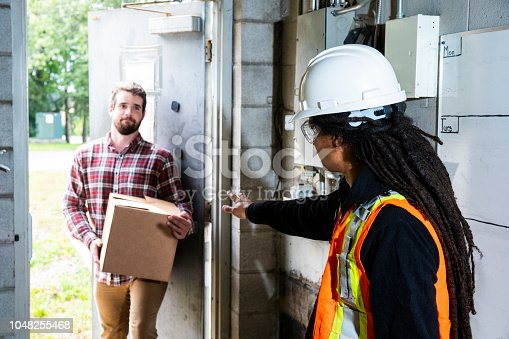 An employee restricting access to a work area that requires protective work wear (PPE)
