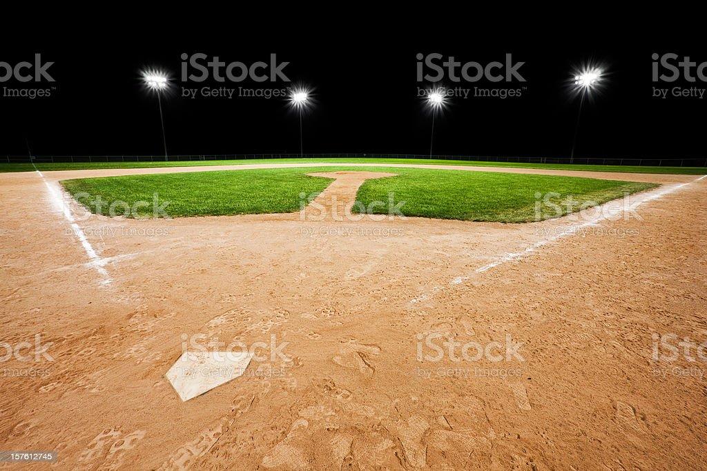 An empty baseball diamond with stadium lights in background royalty-free stock photo