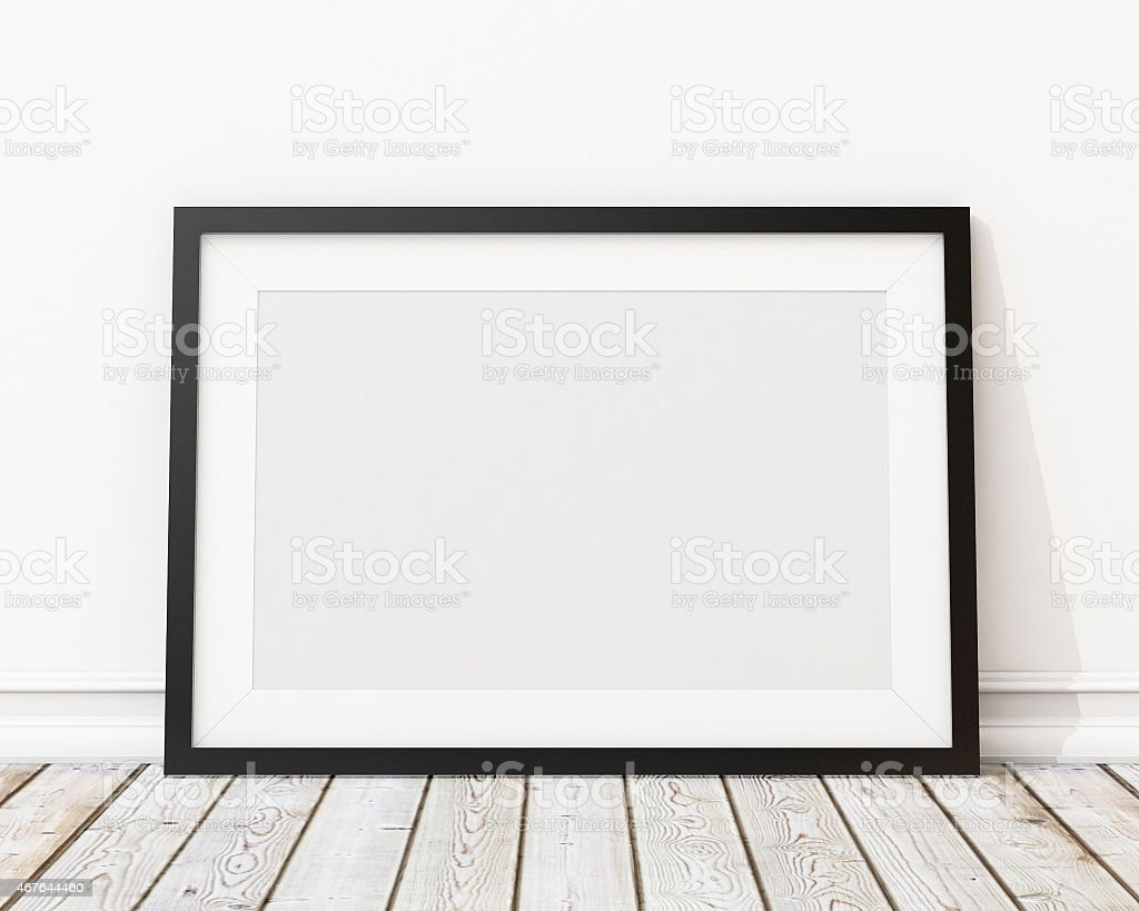 An empty black picture frame leaning against a wall bildbanksfoto