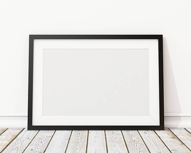 An empty black picture frame leaning against a wall stock photo