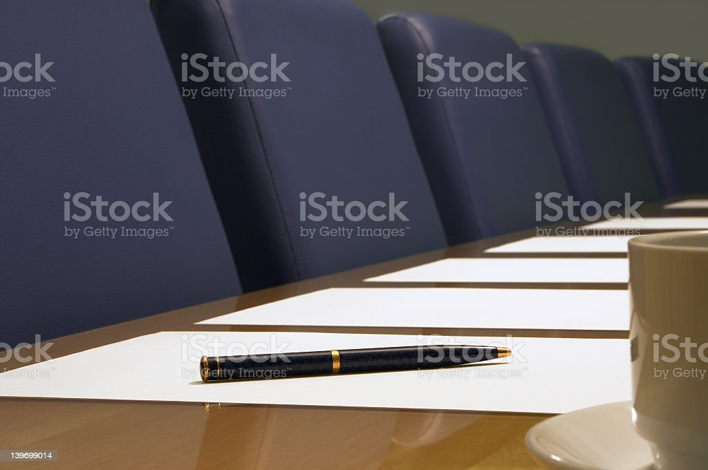 An empty boardroom with white pages on the table stock photo