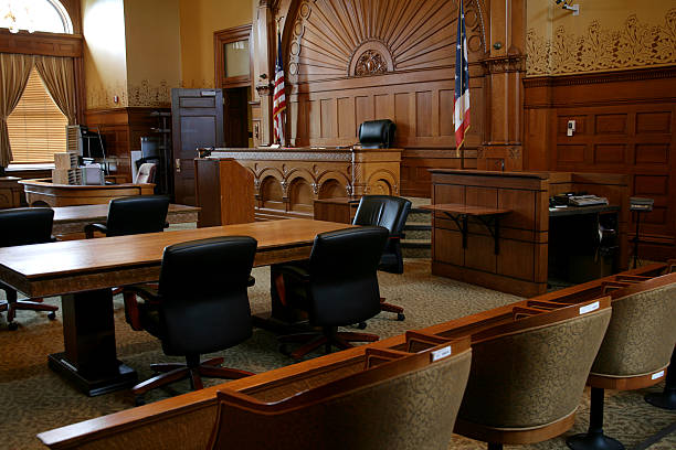 An empty, brown-paneled courtroom with flags Courtroom courtroom stock pictures, royalty-free photos & images