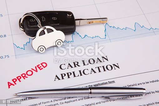 512011833istockphoto An empty car loan form with car key and a pen 917522110