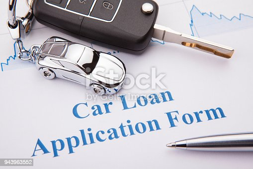 512011833istockphoto An empty car loan form with car key and a pen 943963552