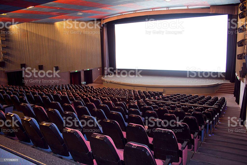 An empty cinema with blank white movie screen stock photo